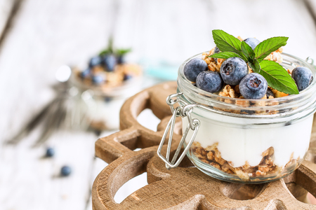 Healthy breakfast of blueberry parfaits made with fresh fruit, Greek yogurt, granola and mint leaves over a rustic cake stand.  Selective focus on glass jar in front with blurred background.