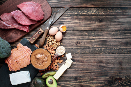 Selection of good fat sources for keto lifestyle. Meat-beef, smoked salmon, eggs, nut butter, nuts, avocado, broccoli, cream cheese, real butter and peanut butter protein.. Ketogenic diet concept