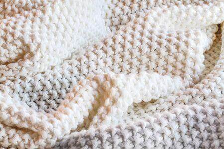 Abstract of a soft knit white and grey throw blanket with selective focus in center with blurred edges.