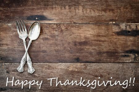 Antique silverware spoon and fork and Happy Thanksgiving text over a rustic old wooden background. Image shot from overhead. Stock Photo