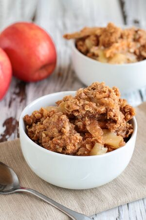 Fresh hot homemade apple crisp or crumble with crunchy streusel topping topped in a bowl with fresh apples in background. Selective focus with blurred background. Stock Photo - 129389009