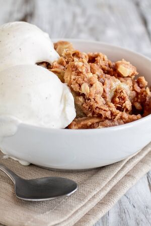 Fresh hot homemade apple crisp or crumble with crunchy streusel topping topped with vanilla bean ice cream. Selective focus with blurred background. Stock Photo