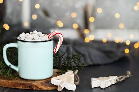 Enamel cup of hot cocoa drink with marshmallows and candy cane against a rustic background with beautiful bokeh lights in front of a window. Wood Christmas tree ornaments in foreground.