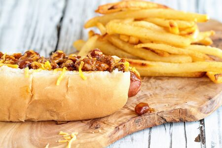 Hot dog with chilli, cheddar cheese and mustard. Selective focus with blurred french fries in the background. Stock Photo