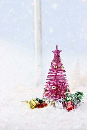 Winter scene of pink retro Christmas tree surrounded by gifts in front of an window. 版權商用圖片