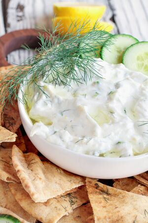 Traditional Greek Tzatziki dip sauce made with cucumber sour cream, Greek yogurt, lemon juice, olive oil and a fresh sprig of dill weed. Served with toasted Zaatar Pita bread. 版權商用圖片