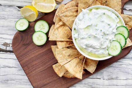 Traditional Greek Tzatziki dip sauce made with cucumber sour cream, Greek yogurt, lemon juice, olive oil and a fresh sprig of dill weed. Served with toasted Zaatar Pita bread.  Top view  or flat lay.