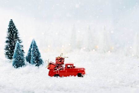 1950s antique vintage red truck hauling a Christmas gifts home through a snowy winter wonder land with pine trees. Extreme shallow depth of field with selective focus on vehicle. 版權商用圖片
