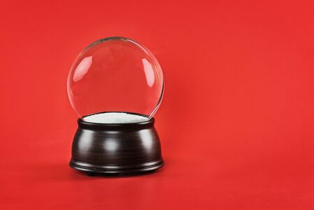 Empty glass snow globe with wooden base against a red background. Free copy space for text included. Stockfoto