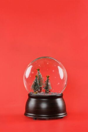 Christmas snow globe with wooden base and bottle brush Christmas trees against a red background. Free copy space for text available.