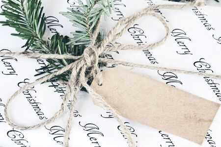Beautiful Christmas gift with blank tag. Decorated naturally with pine tree twigs and twine.