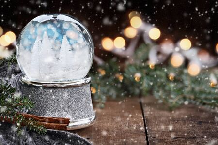Rustic image of a snow globe surrounded by pine branches, cinnamon sticks and a warm gray scarf with falling snow. Shallow depth of field with selective focus on snowglobe.
