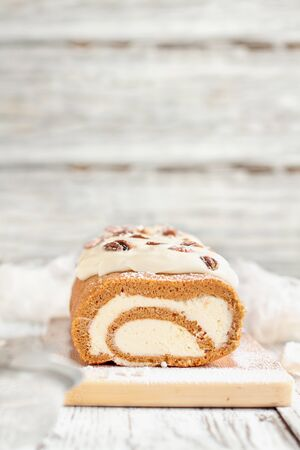 Beautiful fresh baked pumpkin spice roll cake with powdered sugar, pecans, cream cheese filling and icing. Extreme selective focus with blurred background. Stock Photo