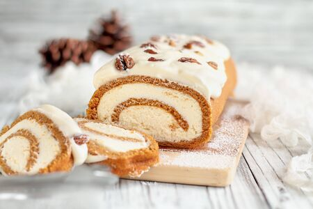 Beautiful fresh baked pumpkin spice roll cake with powdered sugar, pecans, cream cheese filling and icing. Extreme selective focus with blurred background. Stock Photo - 129387786