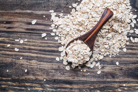 Healthy raw uncooked quick oat flakes in a wooden spoon over a wood table background. Shot from top view. Stock Photo - 129387798