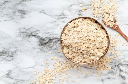 Healthy raw uncooked quick oat flakes in a wooden bowl over a marble table background. Shot from top view. Stock Photo - 129387796