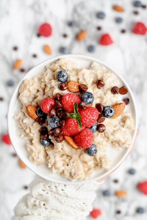 Healthy oatmeal served with berries, chocolate chips, almonds and honey. Bowl held in a womans hand over a marble table background. Shot from top view. 스톡 콘텐츠