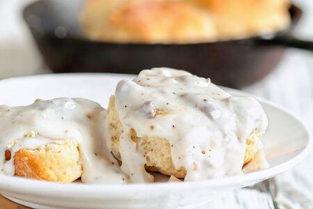 Amerikanische Kekse von Grund auf mit dicker Weißwurstsauce bedeckt. Selektiver Fokus mit Gusseisenpfanne/Pfanne im Hintergrund über einem weißen Tisch.