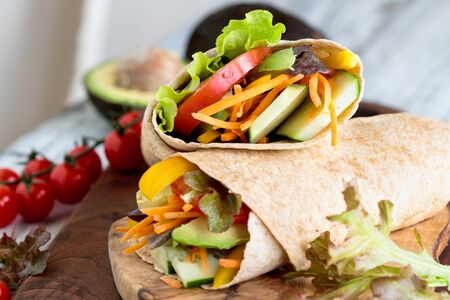 A healthy lunch or dinner of a vegan  vegetarian wrap made with  argula lettuce, sliced tomatoes, cucumbers, avocado, bell peppers and carrots. Selective focus on sandwich on top.  版權商用圖片