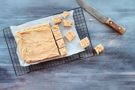 Block of delicious, homemade peanut butter fudge being cut into squares over a textured wood table background with old knife. Image shot from above.  Imagens