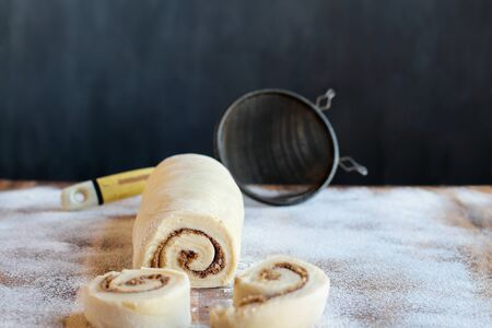 Homemade cinnamon roll dough over a floured surface with duster in background. Selective focus on center of pastry with blurred foreground and background.