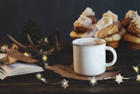 Hot, steaming cup of coffee with cinnamon rolls and open book Selective focus on drink with extreme blurred foreground and background.