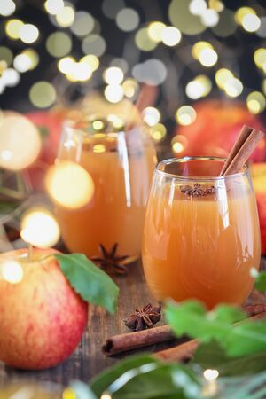 Fresh apple cider drink with star of anise and cinnamon. Selective focus on juice with extreme blurred background and foreground.
