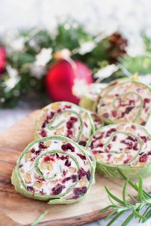 Fresh homemade cranberry pinwheels made with cream cheese, dried cranberries, walnuts, goats cheese and rosemary ready for the holidays. Selective focus with blurred background.