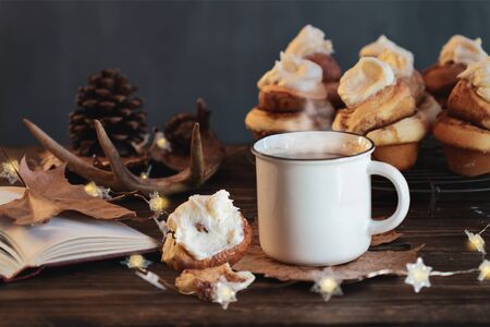 Hot, steaming cup of coffee with cinnamon roll and open book Selective focus on drink with extreme blurred foreground and background.