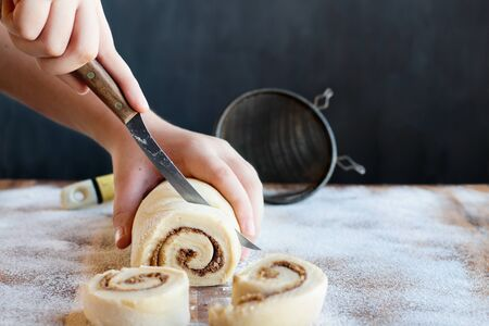 Womans hands cutting homemade cinnamon roll dough over a floured surface with duster in background. Selective focus with blurred foreground and background.  版權商用圖片