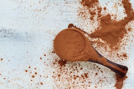 Wooden measuring spoon filled with cinnamon powder over a messy white wood background ready for holiday baking. Image shot from top view. 版權商用圖片