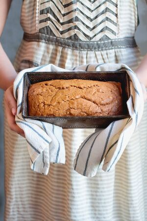 Young womans hands holding a freshly baked loaf of homemade pumpkin bread baked in a vintage bread pan. Selective focus on sweet bread with blurred background.