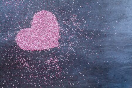Abstract of a pink and white heart made of tiny beads ober a black background.  Top view.  版權商用圖片