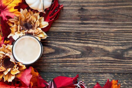Delicious hot, steaming cup or mug of coffee with cream over a rustic wood table background and surrounded by autumn leaves, red plaid scarf, flowers and white mini pumpkins.  版權商用圖片