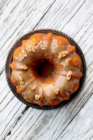 Delicious, Pumpkin Spice Bundt Cake frosted with brown sugar frosting and walnuts oven a rustic wood table background.  Top down view.