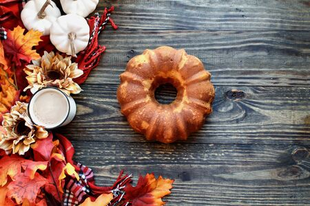Delicious, naked pumpkin spice bundt cake with Autumn leaves and coffee over a rustic woode table background. Image shot from top view..