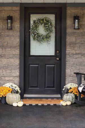 Porche delantero decorado para el Día de Acción de Gracias con corona casera colgada en la puerta. Calabazas tradicionales, calabazas blancas y mamás que dan un ambiente acogedor. Foto de archivo
