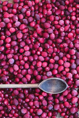 Background of frozen preserved fresh cranberries with vintage wooden spoon. Image shot from top view.
