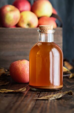 Apple cider vinegar with the mother, yeast and healthy bacteria, surrounded by fresh apples. Apple cider vinegar has long been used in naturopathy to treat things such as diabetes and high cholesterol.