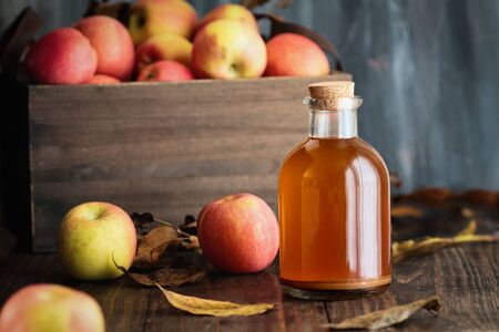 Apple cider vinegar with the mother, yeast and healthy bacteria, surrounded by fresh apples. Apple cider vinegar has long been used in naturopathy to treat things such as diabetes and high  cholesterol. 版權商用圖片