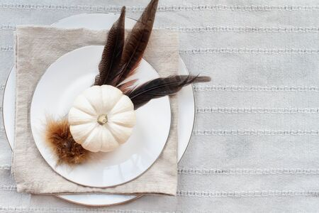 Thanksgiving Day place setting with white plates, mini white pumpkins, Pheasant feathers and napkin over grey table runner.