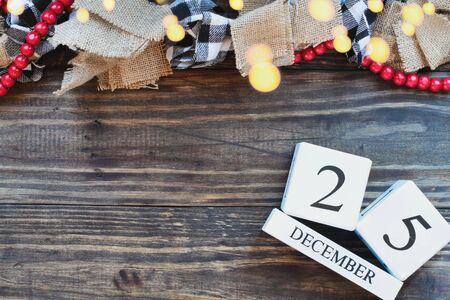 December 25 background. Wood calendar blocks with the date December 25th to mark Christmas Day with bokeh lights, black and white buffalo check and red bead garland. Top view with copy space available.