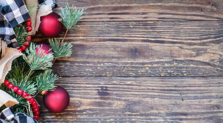 Christmas background with holiday trimmings of pine tree branches, ornaments, black and white buffalo check ribbon, burlap and red bead garland.. Top view with copy space available.