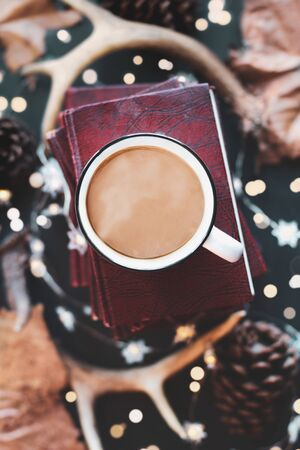 Hot, steaming cup of coffee over a stack of books with dried autumn leaves, deer antlers, pines cones, and sparkling lights. Selective focus on mug with extreme blurred background. Top view.