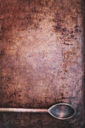 Overhead view of vintage wood spoon over scratched grunge sheet of copper metal texture with light vignetting.  版權商用圖片