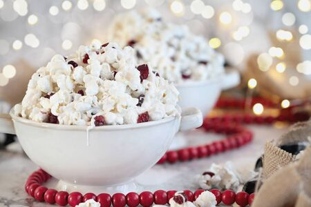 Bowls of homemade popcorn and dried cranberry snack covered in white chocolate ready for the holidays surrounded by bokeh lights and red bead garland.. Selective focus with blurred background.