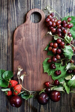 Beautiful solid walnut cutting board with fresh, red, organic homegrown fruit. Plums, grapes and strawberries. Top view. Overhead.