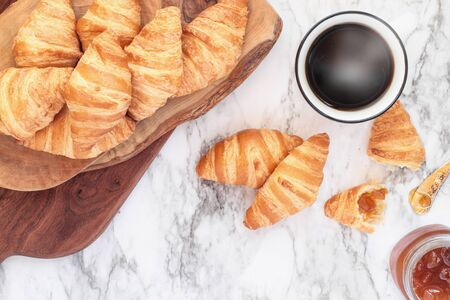 Fresh homemade croissants or crescent rolls with jam and a cup of coffee over marble background Image shot from top view.