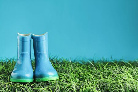 Blue childrens rain boots  wellies sitting in the grasss agaisnt a blue background with room for copy space.