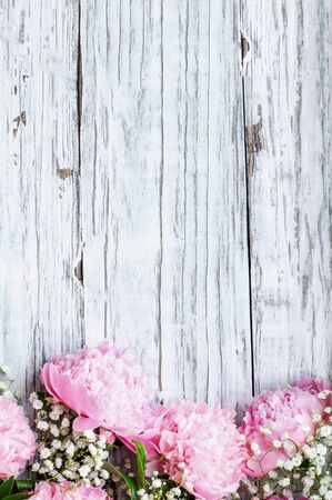 Bouquet of pink Peonies and Babys Breath flowers over a white rustic wood table background  with copy space for your text. Flat lay. Stockfoto